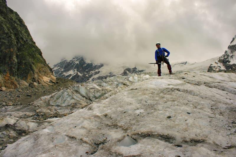 Ο ορεσίβιος με το τσεκούρι πάγου στέκεται πάνω από τον παγετώνα στοκ φωτογραφίες με δικαίωμα ελεύθερης χρήσης