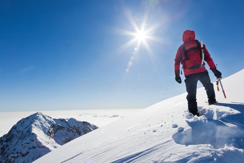Ο ορεσίβιος φθάνει στην κορυφή ενός χιονώδους βουνού σε ένα ηλιόλουστο winte στοκ εικόνα με δικαίωμα ελεύθερης χρήσης