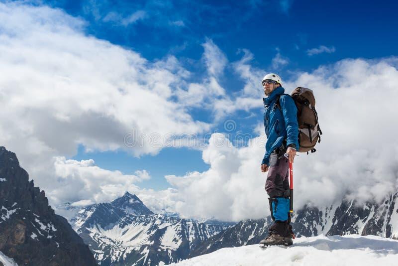 Ο ορεσίβιος φθάνει στην κορυφή ενός χιονώδους βουνού σε μια ηλιόλουστη χειμερινή ημέρα στοκ εικόνες