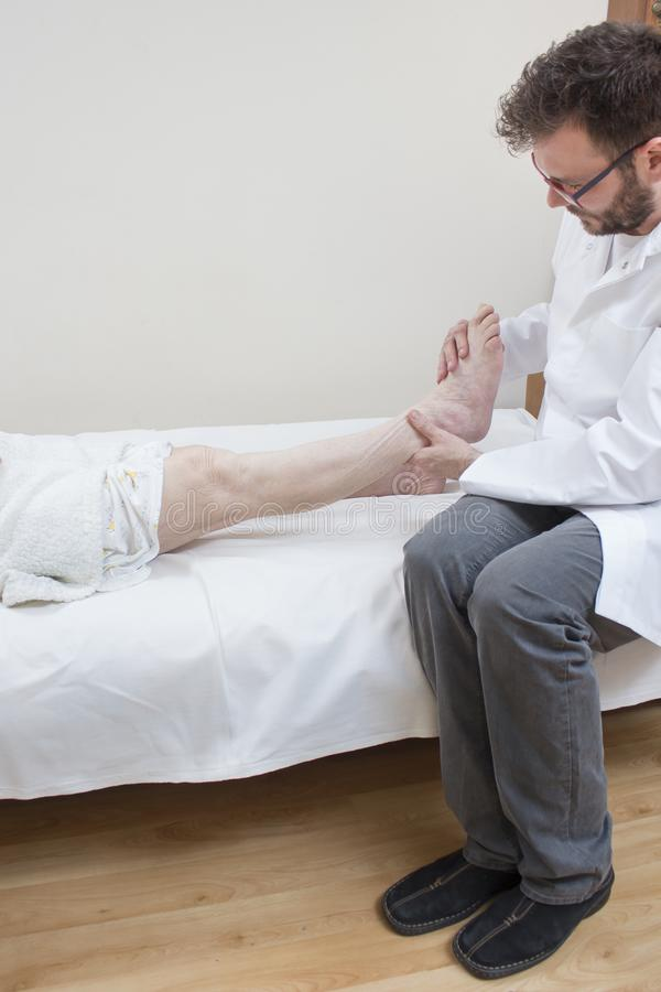 Ο ορθοπεδικός γιατρός εξετάζει το πόδι μιας ηλικιωμένης γυναίκας στοκ εικόνα με δικαίωμα ελεύθερης χρήσης