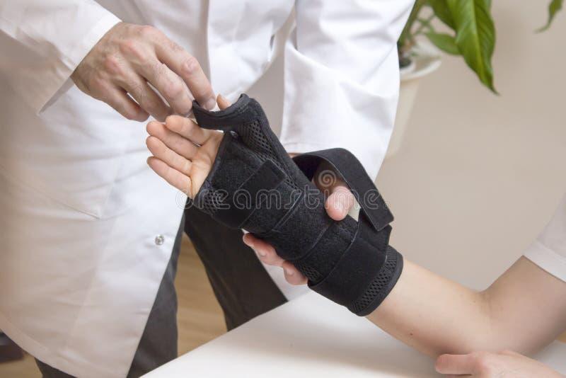 Ο ορθοπεδικός χειρούργος υποθέτει έναν σταθεροποιητή για το χέρι της γυναίκας στοκ εικόνες
