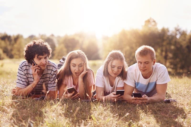 Ο οριζόντιος πυροβολισμός τεσσάρων φίλων της ίδιας ηλικίας, που στρέφονται στις οθόνες των κινητών τηλεφώνων, έχει τις διαφορετικ στοκ φωτογραφία με δικαίωμα ελεύθερης χρήσης