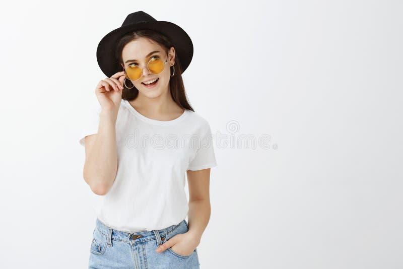 Ο οριζόντιος πυροβολισμός της ξένοιαστης θηλυκής και flirty φίλης στα γυαλιά ηλίου, τα σκουλαρίκια και το μοντέρνο καπέλο, κράτημ στοκ εικόνα με δικαίωμα ελεύθερης χρήσης
