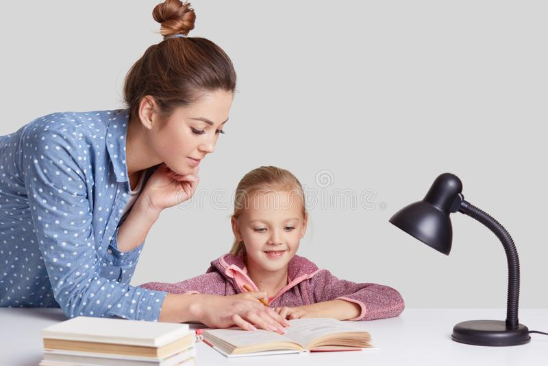 Ο οριζόντιος πυροβολισμός της σοβαρής νέας μητέρας διδάσκει τη μικρή ελαφριά μαλλιαρή κόρη της για να διαβάσει, παρουσιάζει κάτι  στοκ φωτογραφία με δικαίωμα ελεύθερης χρήσης