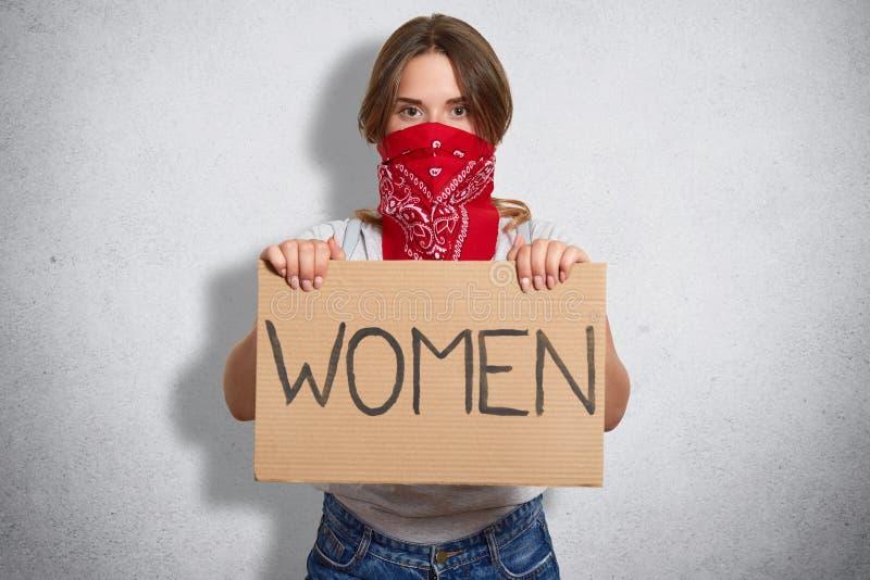 Ο οριζόντιος πυροβολισμός της όμορφης φεμινίστριας κρατά το πιάτο με τις γυναίκες επιγραφής, ανήκει στην ειδική κίνηση, καλύπτει  στοκ φωτογραφία