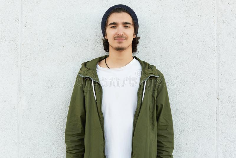 Ο οριζόντιος πυροβολισμός του μοντέρνου εφήβου φορά το μαύρο καπέλο, άσπρη μπλούζα και το πράσινο ανοράκ, κοιτάζει με τη ικανοποι στοκ φωτογραφία με δικαίωμα ελεύθερης χρήσης