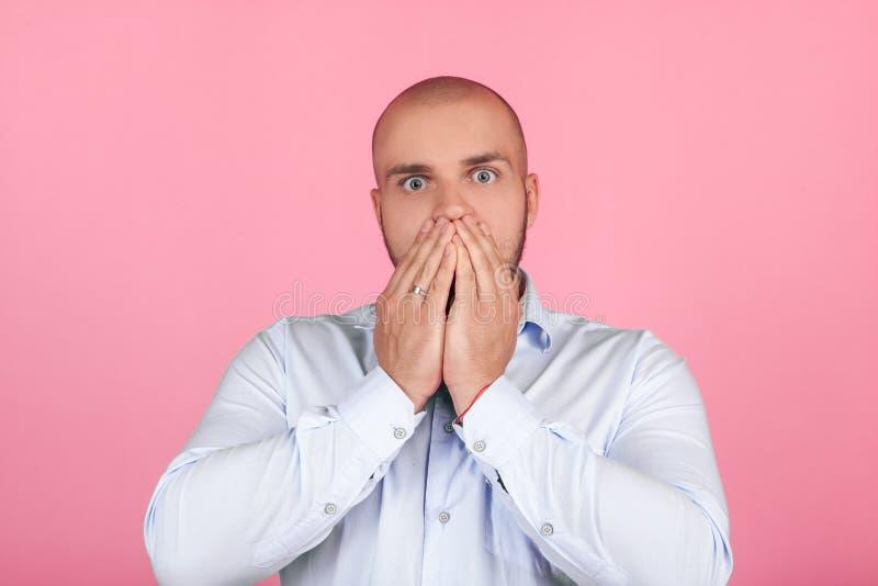 Ο οριζόντιος πυροβολισμός των έκπληκτων μοντέρνων τύπων ή ο συνάδελφος κρατά τα χέρια στα mouthes, κοιτάζει επίμονα στη κάμερα, α στοκ εικόνες