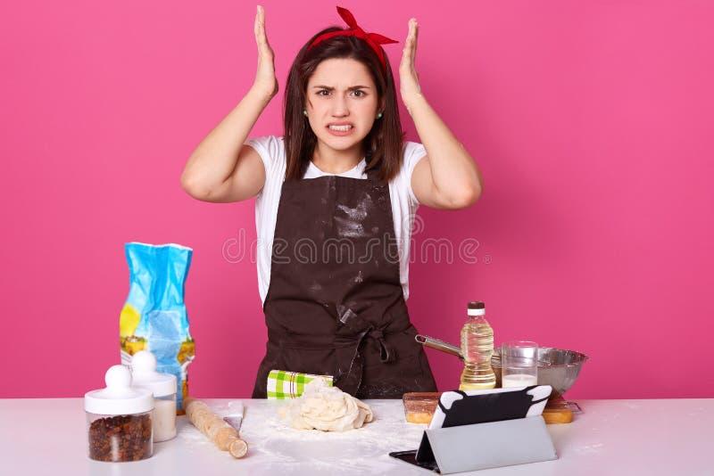 Ο οριζόντιοσης πυροβολισμός της νοικοκυράς, κυρία που φορά την καφετιά ποδιά βρώμικη με το αλεύρι, άσπρη περιστασιακή μπλούζα, κό στοκ φωτογραφίες