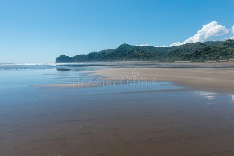 Ο ουρανός και τα σύννεφα απεικόνισαν στην υγρή άμμο στην παραλία Piha στοκ φωτογραφίες με δικαίωμα ελεύθερης χρήσης