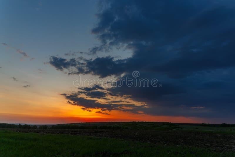 Ο ουρανός με τα φωτεινά σύννεφα αναμμένα από τον ήλιο μετά από το ηλιοβασίλεμα πέρα από τον τομέα στοκ εικόνες