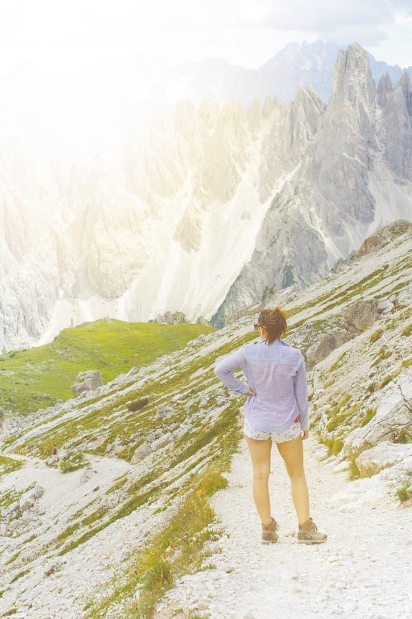 Ο οδοιπόρος γυναικών βρίσκεται έχει ένα υπόλοιπο βουνά Αιχμές όπως ένα υπόβαθρο ημέρα ηλιόλουστη οδοιπορία Φλόγα φακών Το επιτυχέ στοκ φωτογραφίες