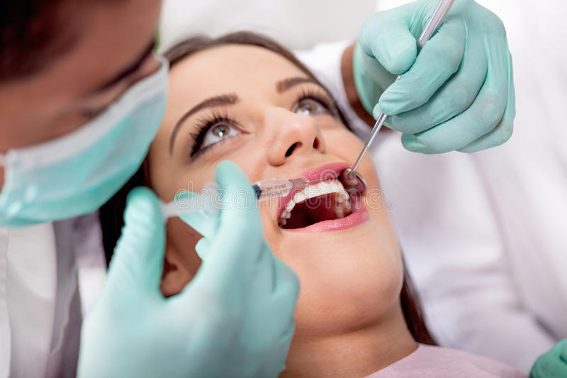 Ο οδοντίατρος δίνει τη σύριγγα αναισθητοποιεί στον ασθενή του στοκ εικόνα