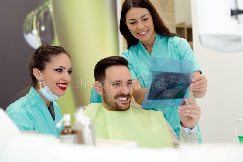 Ο οδοντίατρος παρουσιάζει υπομονετική των ακτίνων X εικόνα στοκ εικόνα με δικαίωμα ελεύθερης χρήσης