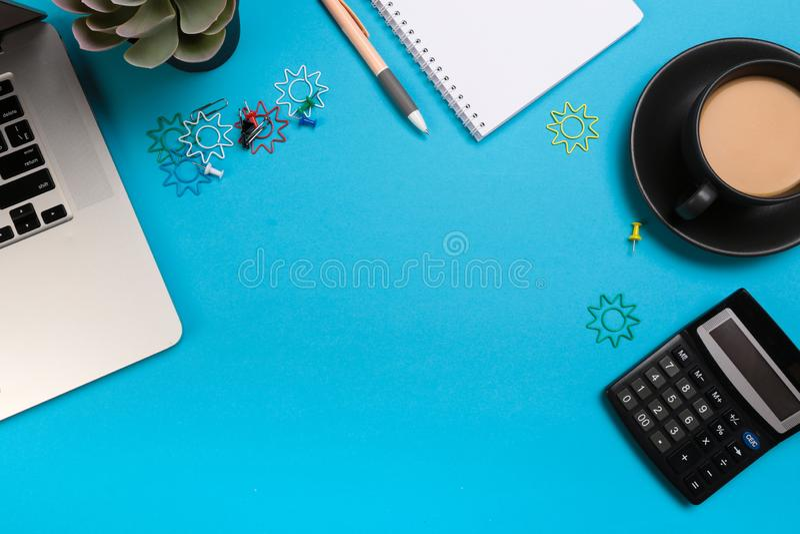 Ο πίνακας γραφείων γραφείων με το σύνολο ζωηρόχρωμων προμηθειών, άσπρο κενό σημειωματάριο, φλυτζάνι, μάνδρα, PC, τσαλάκωσε το έγγ στοκ εικόνα με δικαίωμα ελεύθερης χρήσης