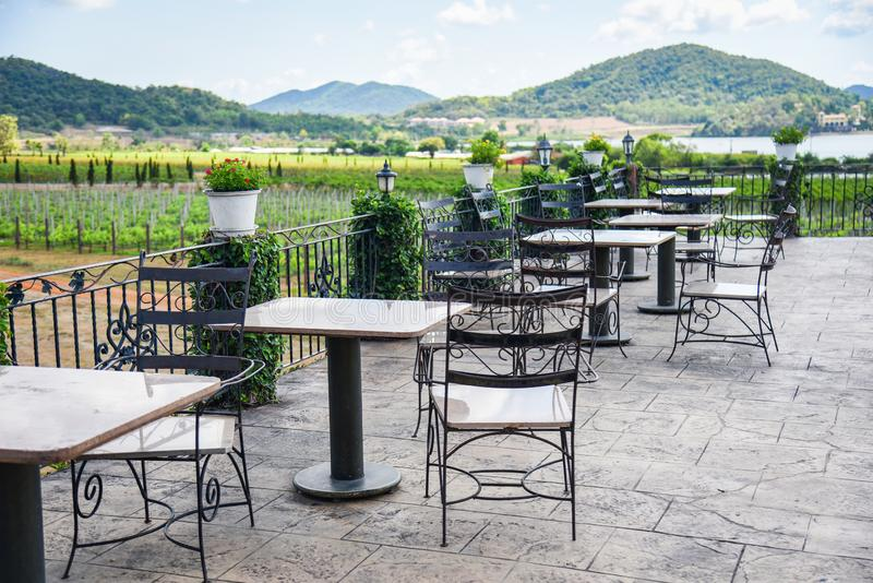 Ο πίνακας και οι καρέκλες στο μπαλκόνι της υπαίθριας φύσης άποψης εστιατορίων καλλιεργούν και του υποβάθρου βουνών - να δειπνήσου στοκ εικόνες