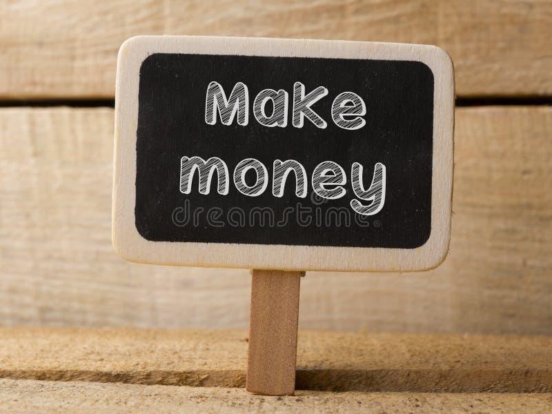 Ο πίνακας κιμωλίας με τη λέξη κάνει τα χρήματα στο ξύλινο υπόβαθρο στοκ εικόνα