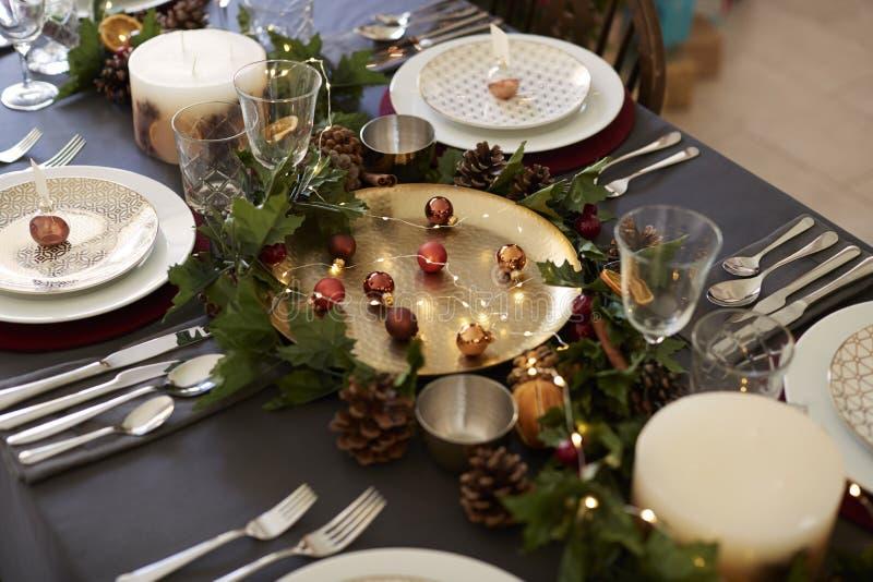 Ο πίνακας Χριστουγέννων που θέτει με τους κατόχους καρτών ονόματος μπιχλιμπιδιών τακτοποίησε στα πιάτα, χρυσό κεντρικό τεμάχιο πι στοκ εικόνα
