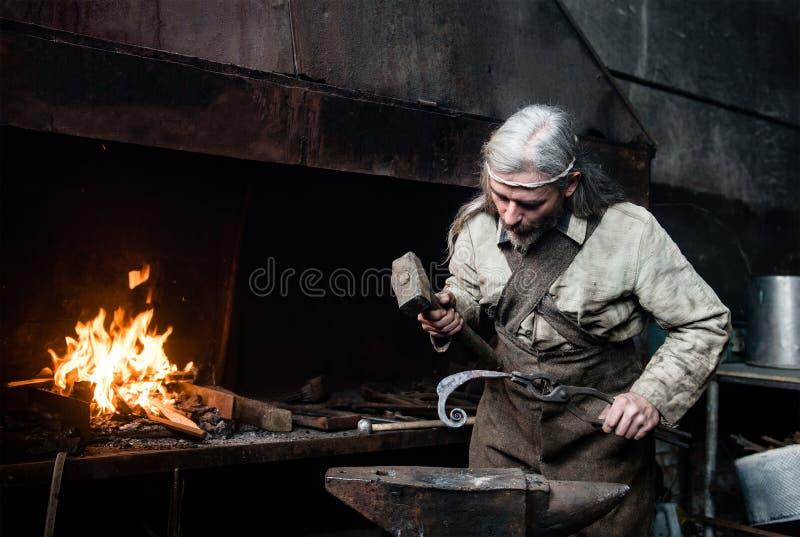 Ο παλαιός σιδηρουργός σφυρηλατεί σφυρηλατεί τα προϊόντα μετάλλων στοκ εικόνες