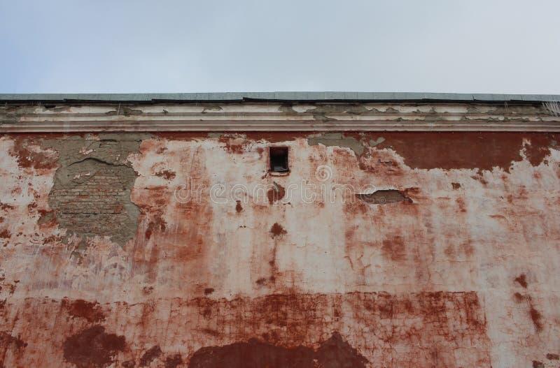 Ο παλαιός τοίχος ενός κτηρίου τούβλου με ένα παράθυρο εξέτασης θρυμμάτισε την πρόσοψη στοκ εικόνα