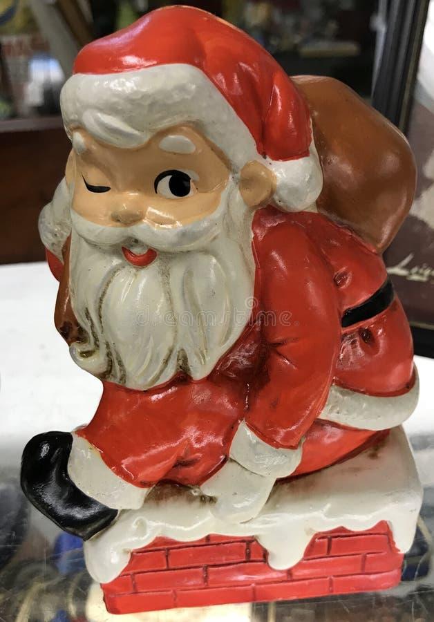 Ο παλιός Άγιος Βασίλης κουβαλάει ένα σάκο παιχνιδιών πάνω σε μια χιονισμένη καμινάδα στοκ εικόνα