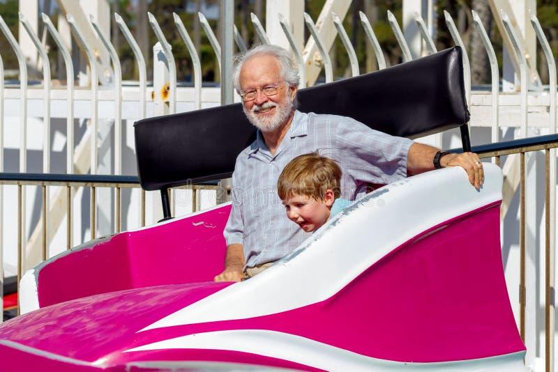 Ο παππούς εξετάζει τη κάμερα χαμογελώντας όπως αυτός και η περιστροφή εγγονών του στοκ φωτογραφία με δικαίωμα ελεύθερης χρήσης