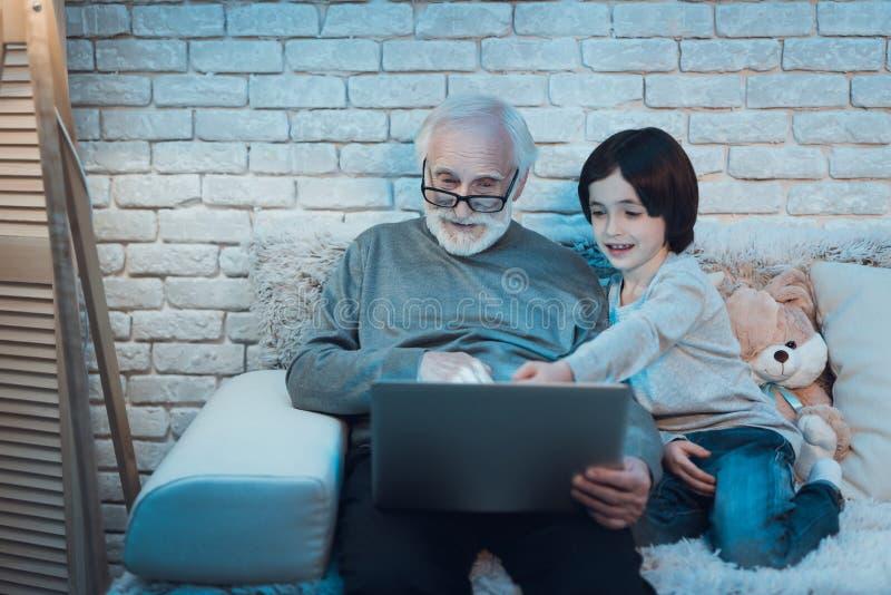 Ο παππούς και ο εγγονός κάθονται τον κινηματογράφο προσοχής τη νύχτα στο σπίτι στοκ εικόνα με δικαίωμα ελεύθερης χρήσης