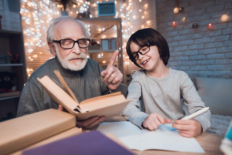 Ο παππούς και ο εγγονός κάνουν την εργασία τη νύχτα στο σπίτι Το Granddad βοηθά το αγόρι στοκ εικόνες με δικαίωμα ελεύθερης χρήσης