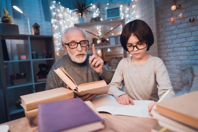 Ο παππούς και ο εγγονός κάνουν την εργασία τη νύχτα στο σπίτι Το Granddad βοηθά το αγόρι στοκ εικόνα με δικαίωμα ελεύθερης χρήσης