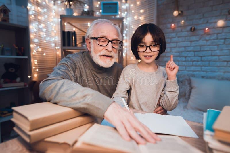 Ο παππούς και ο εγγονός κάνουν την εργασία τη νύχτα στο σπίτι Το Granddad βοηθά το αγόρι στοκ εικόνες