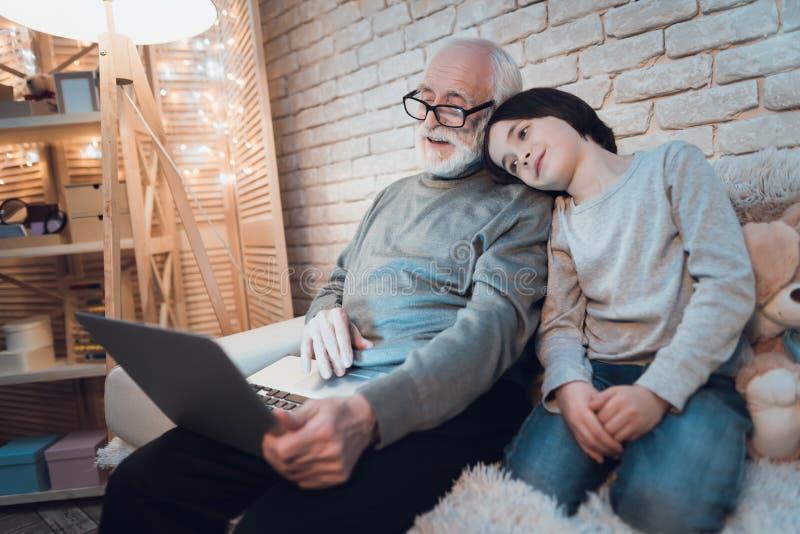 Ο παππούς και ο εγγονός μιλούν στο skype με την οικογένεια τη νύχτα στο σπίτι στοκ εικόνες