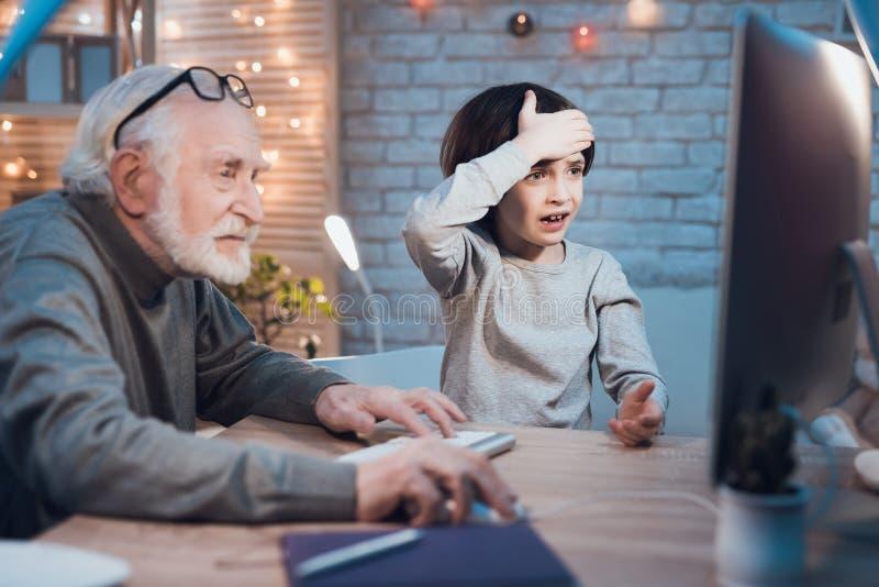 Ο παππούς και ο εγγονός παίζουν τα παιχνίδια στον υπολογιστή τη νύχτα στο σπίτι Το αγόρι είναι ενθαρρυντικό για το granddad στοκ φωτογραφίες