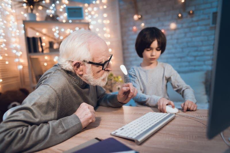 Ο παππούς και ο εγγονός παίζουν τα παιχνίδια στον υπολογιστή τη νύχτα στο σπίτι στοκ εικόνα με δικαίωμα ελεύθερης χρήσης