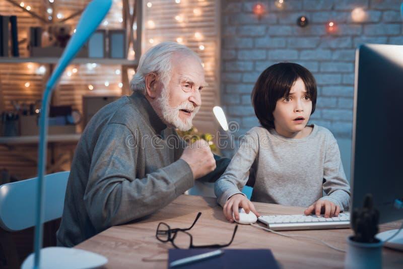 Ο παππούς και ο εγγονός παίζουν τα παιχνίδια στον υπολογιστή τη νύχτα στο σπίτι Το Granddad είναι ενθαρρυντικό για το αγόρι στοκ εικόνα με δικαίωμα ελεύθερης χρήσης