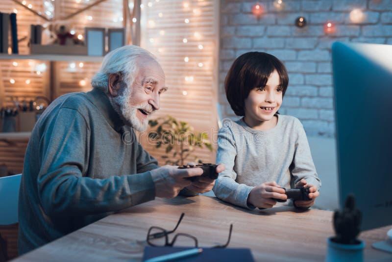 Ο παππούς και ο εγγονός παίζουν τα τηλεοπτικά παιχνίδια στον υπολογιστή τη νύχτα στο σπίτι στοκ φωτογραφίες