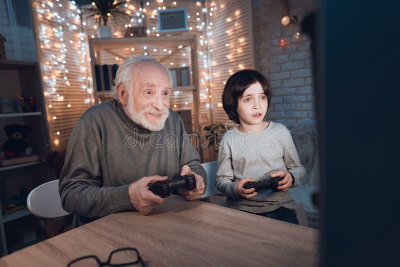 Ο παππούς και ο εγγονός παίζουν τα τηλεοπτικά παιχνίδια στον υπολογιστή τη νύχτα στο σπίτι στοκ εικόνες με δικαίωμα ελεύθερης χρήσης
