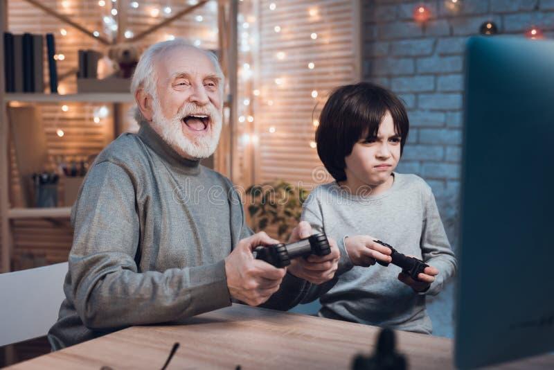 Ο παππούς και ο εγγονός παίζουν τα τηλεοπτικά παιχνίδια στον υπολογιστή τη νύχτα στο σπίτι στοκ φωτογραφία