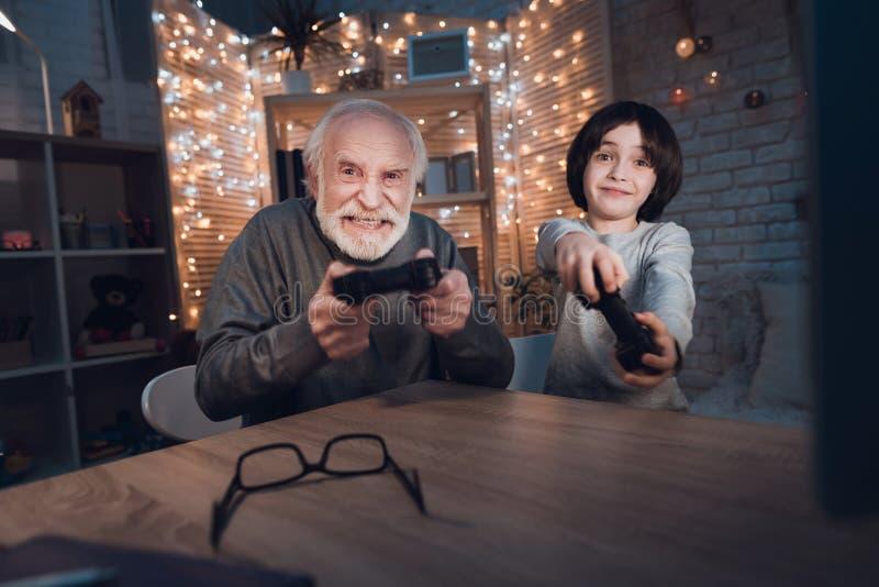 Ο παππούς και ο εγγονός παίζουν τα τηλεοπτικά παιχνίδια τη νύχτα στο σπίτι στοκ φωτογραφίες με δικαίωμα ελεύθερης χρήσης