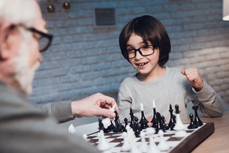Ο παππούς και ο εγγονός παίζουν το σκάκι μαζί τη νύχτα στο σπίτι στοκ φωτογραφία με δικαίωμα ελεύθερης χρήσης