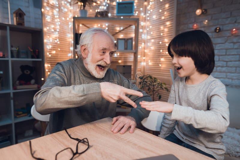 Ο παππούς και ο εγγονός παίζουν το ψαλίδι εγγράφου βράχου τη νύχτα στο σπίτι στοκ φωτογραφία
