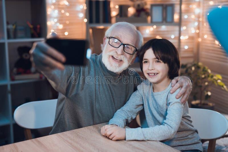 Ο παππούς και ο εγγονός παίρνουν selfie στο τηλέφωνο τη νύχτα στο σπίτι στοκ εικόνες