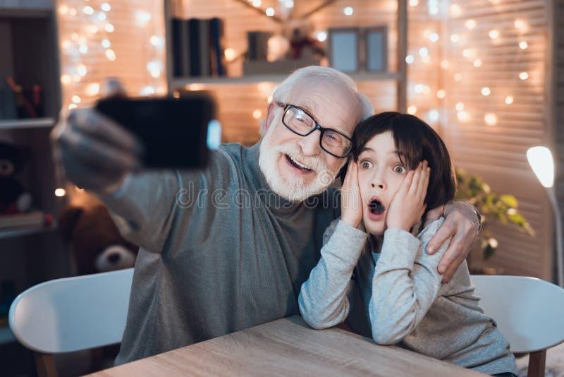 Ο παππούς και ο εγγονός παίρνουν selfie τη νύχτα στο σπίτι στοκ φωτογραφία με δικαίωμα ελεύθερης χρήσης
