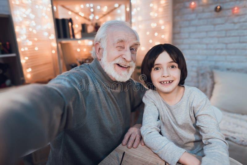 Ο παππούς και ο εγγονός παίρνουν selfie τη νύχτα στο σπίτι στοκ εικόνα με δικαίωμα ελεύθερης χρήσης