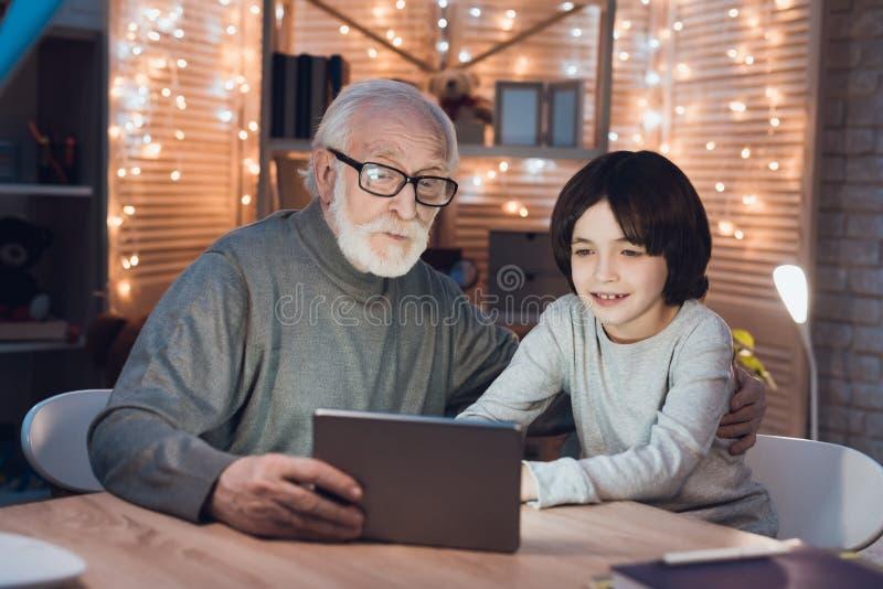 Ο παππούς και ο εγγονός προσέχουν τον ενδιαφέροντα κινηματογράφο τη νύχτα στο σπίτι στοκ φωτογραφία με δικαίωμα ελεύθερης χρήσης