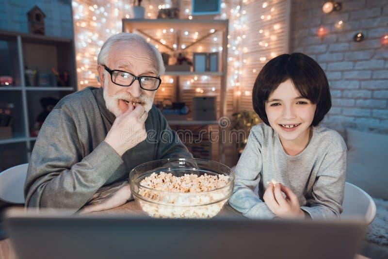 Ο παππούς και ο εγγονός προσέχουν τον κινηματογράφο με popcorn τη νύχτα στο σπίτι στοκ φωτογραφία