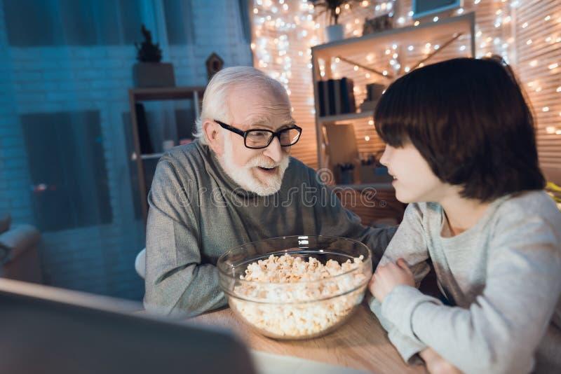 Ο παππούς και ο εγγονός προσέχουν τον κινηματογράφο με popcorn τη νύχτα στο σπίτι στοκ φωτογραφία με δικαίωμα ελεύθερης χρήσης