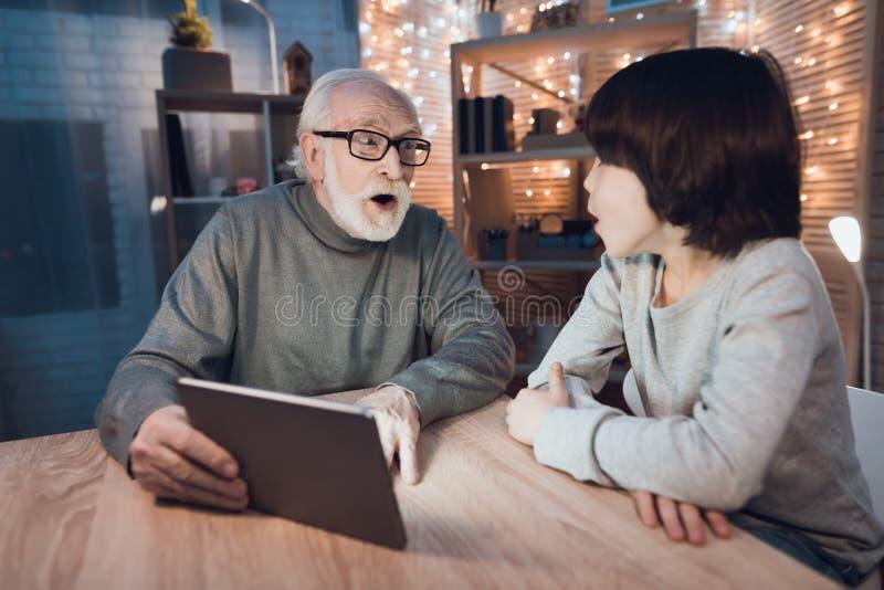 Ο παππούς και ο εγγονός προσέχουν το τρομακτικό κινηματογράφο στο lap-top τη νύχτα στο σπίτι στοκ φωτογραφίες με δικαίωμα ελεύθερης χρήσης