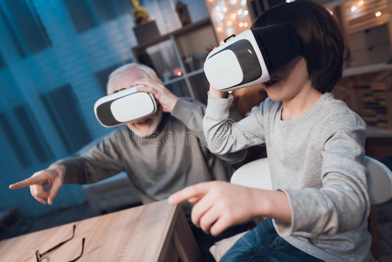 Ο παππούς και ο εγγονός χρησιμοποιούν την εικονική πραγματικότητα τη νύχτα στο σπίτι στοκ εικόνες