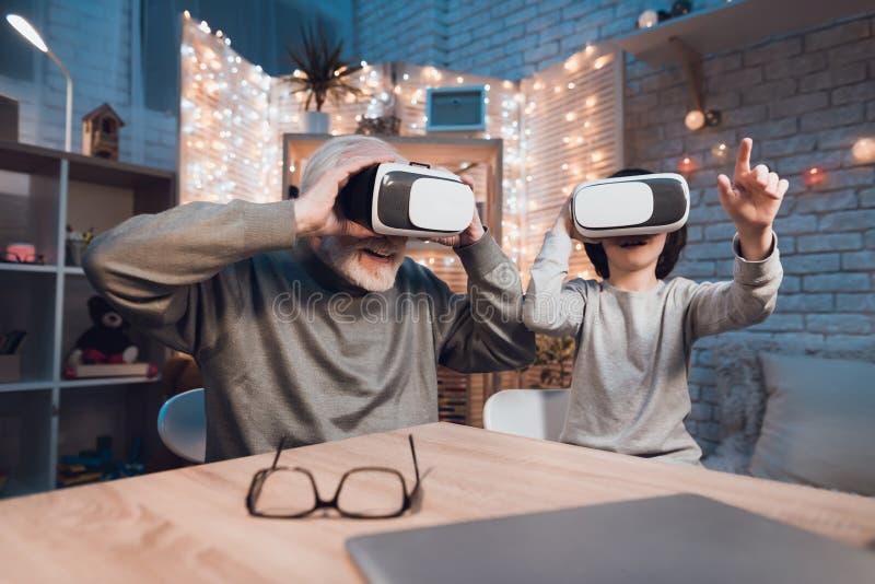 Ο παππούς και ο εγγονός χρησιμοποιούν την εικονική πραγματικότητα τη νύχτα στο σπίτι στοκ φωτογραφία με δικαίωμα ελεύθερης χρήσης