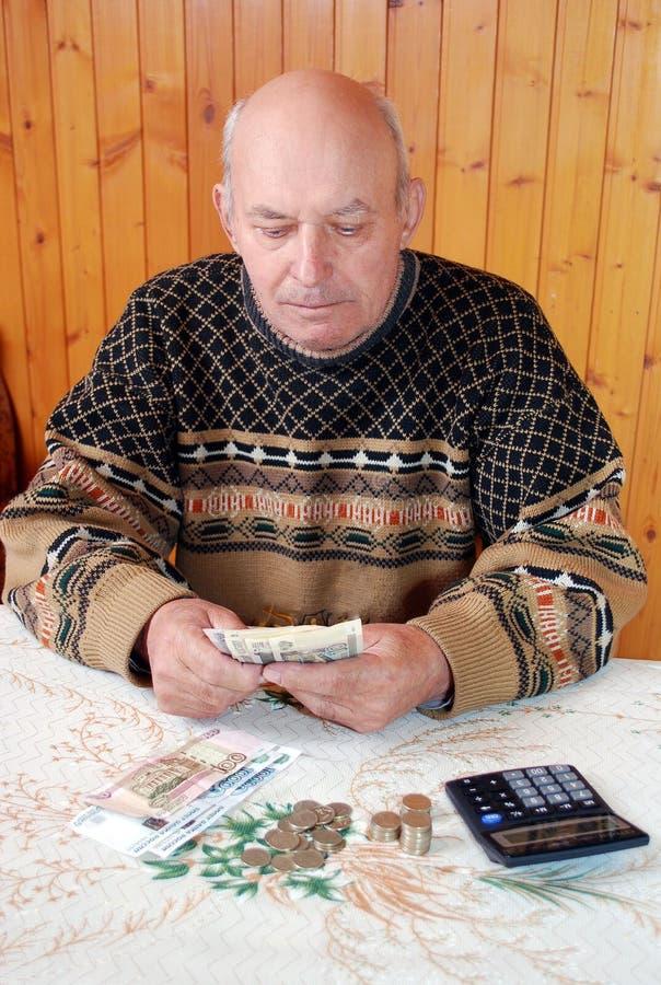 Ο παππούς σε ένα πουλόβερ κάθεται στο dacha σε έναν πίνακα και μετρά τα χρήματα στοκ φωτογραφία