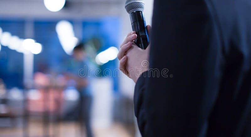 Ο παρουσιαστής σεμιναρίου κρατά μικρόφωνο σε συνέδριο για την ομιλία Ομιλητής που δίνει διάλεξη στο κοινό των επιχειρήσεων στοκ φωτογραφία